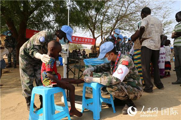 2020年3月7日,中国第六批赴南苏丹(朱巴)维和步兵营医护人员为驻地民众进行卫生防病义诊活动。图为医护人员皇后村爱心义诊中为儿童进行外伤消毒。(李欣 摄)